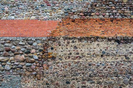 the abstract textured background of an old wall in vintage style from stones and bricks