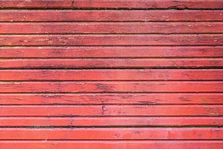 the old painted texture of the panel from wooden boards for a background or for wallpaper of red color in retro style