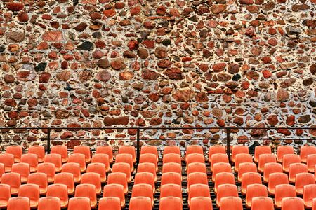 rows of seats for the audience in the foreground outdoors and against the background of an ancient stone wall