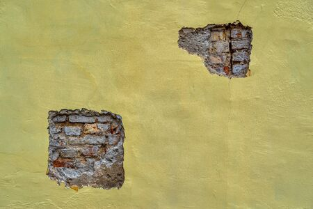part of the plastered brick wall with two spotty destructions or with local superficial damages for a vintage background or for wallpaper 스톡 콘텐츠
