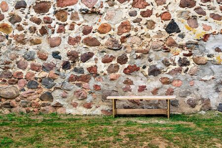 one small bench from a wooden board is located on the earth with a grass and against the background of an ancient stone wall