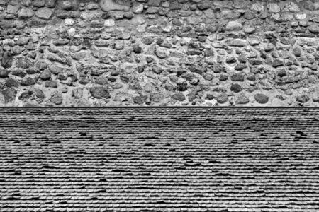 The texture of the wooden tiles in the foreground and the texture of the old stone wall in the background of monochrome tone.
