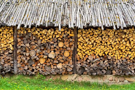 Stack of firewood with the textured end faces under an old wooden canopy.