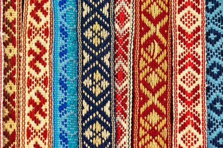 The weaved fabric with the textured ethnic belarusian pattern closeup for an abstract background or for wallpaper.