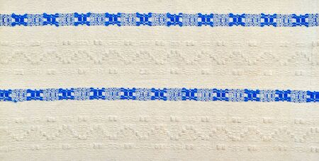 The white weaved fabric with the blue textured ethnic pattern for an abstract background or for wallpaper.