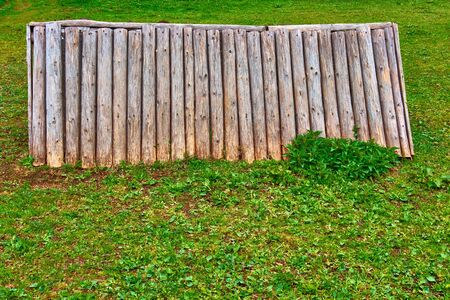 Old wooden structure or separate insulated part of log wall on green lawn