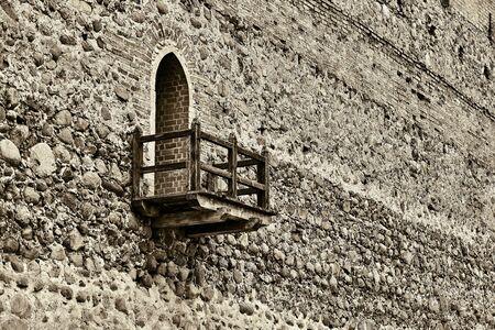 Antico muro di pietra della fortezza con un'uscita sul balcone in legno per l'osservazione in stile vintage seppia