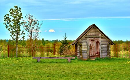One old wooden hut on the green lawn and amid a blue sky with horizon