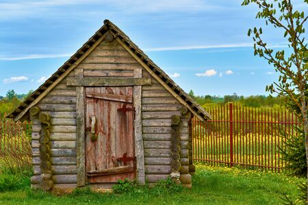 One old wooden hut closeup on green lawn and amid blue sky with horizon Stockfoto