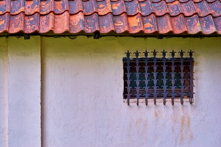 Part of an old house with roof tiles and one window with a forged figure grille closeup on a plastered wall