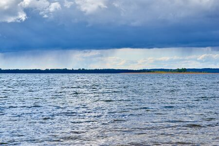Summer thunderstorm landscape on the river or on the lake with frowning pasmure sky and with clouds