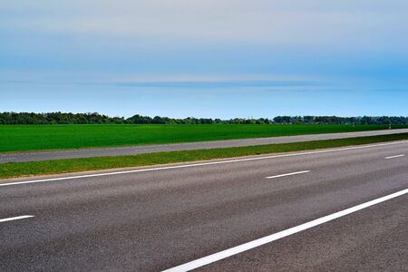 Asphalt road or highway closeup against the background of rural landscape with green sown field and forest on the horizon of blue sky