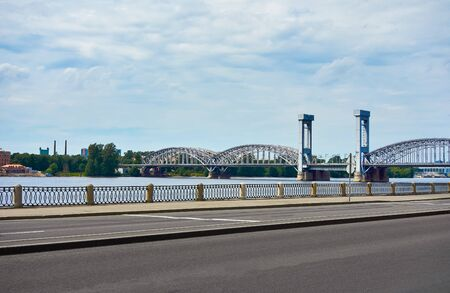 cityscape with a large and old railway bridge against the sky and an empty highway on the waterfront in the foreground
