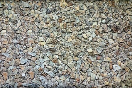 the rough textured surface of the spotted background is covered with abstract shaped stones 写真素材