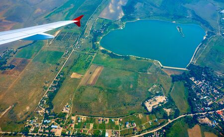 the wing of the aircraft on the background of the landscape and panoramic view of the earth from a height of flight