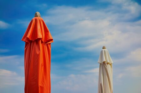 two closed beach umbrella red and white color closeup amid blue skies 写真素材