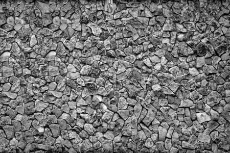 rough textured background surface covered with stones abstract shape of monochrome tone