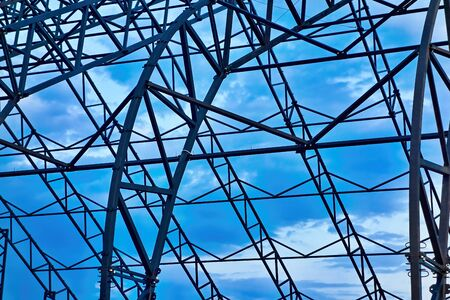 Abstract metal structure closeup against the background of blue sky