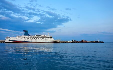 one white ship stands in the seaport at the old pier in the background against the blue sky and blue water 写真素材