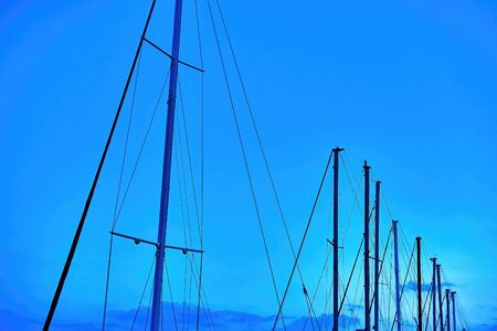 the tops of the yacht masts against the evening dark blue sky for abstract background