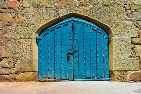 ancient stone wall for vintage background with old wooden gate closeup
