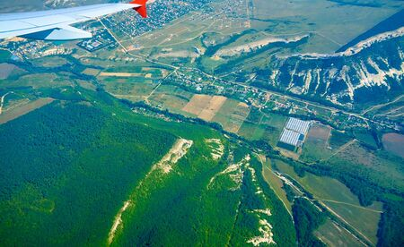 panoramic view of the earth from the height of flight and the wing of the aircraft on the background of the landscape