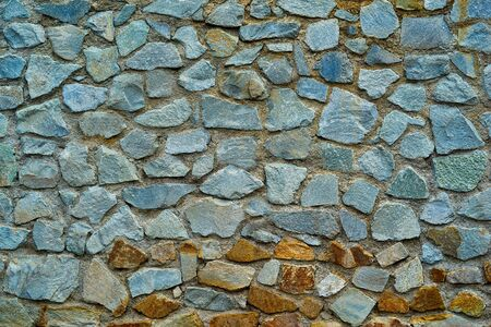 Abstract textured spotted surface background of part of old stone wall