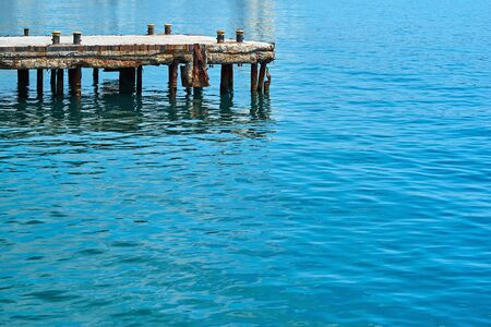 old concrete sea berth or pier for boats and yachts and calm sea water surface