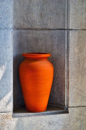 one large red clay vase or jug closeup is located in a niche stone wall outdoors