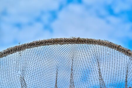 part of an old net made of strands or mesh on the metal hoop and against the blue sky