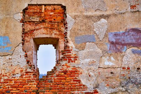 old outer brick wall of an ancient building with an end to end hole with access to the street through all subsequent walls and partitions Imagens