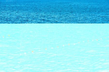 continuous seawater surface of blue with a small wave and small buoys in a row for fencing and safety Banco de Imagens