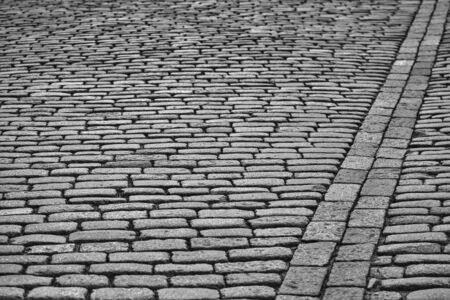 old stone pavement made of monochrome cobbling for vintage textured background