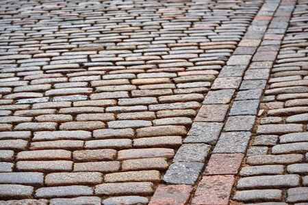 old stone pavement of cobblestone for textured background with sharpness in the foreground at the bottom