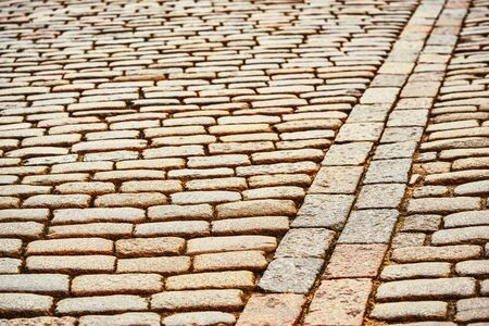 old stone pavement made of beige cobbling for vintage textured background Banco de Imagens