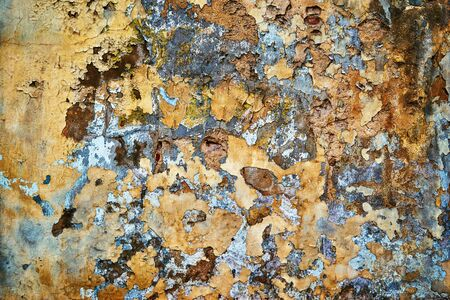 exfoliating or peeling and weathered plaster on the wall for abstract background and wallpaper