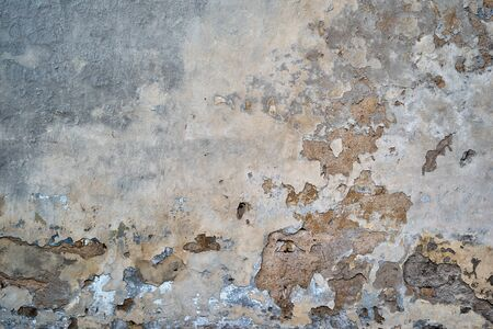 abstract exfoliating or peeling and weathered plaster on the wall for background and wallpaper