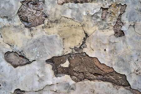 the abstract destroyed old plaster on a wall for a background or for wallpaper