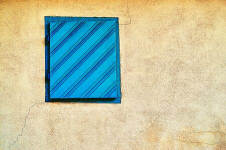 one old shuttered window or a small closed door on an old plastered wall wall closeup Banco de Imagens