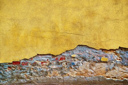 old brick wall with damaged and destroyed stucco at the bottom of the wall for vintage background closeup Banco de Imagens