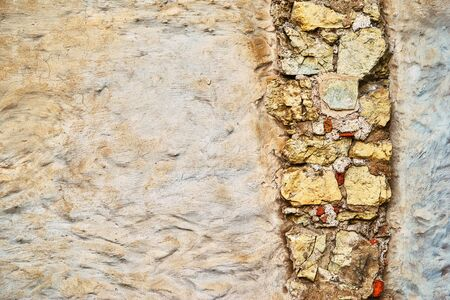 empty surface of old plastered wall for background with textured vertical piece of masonry Banco de Imagens