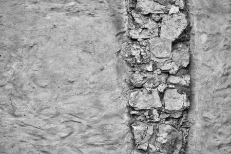 empty monochrome surface of old plastered wall for background with textured vertical piece of masonry Banco de Imagens