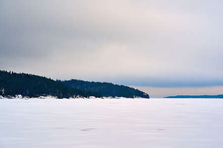 winter landscape with gray sky and white snow on a large lake or in a clear field and with forest on a hilly horizon Stock fotó