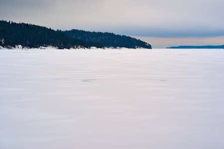 winter landscape with white snow on a large lake or in a clear field and with forest on a hilly horizon