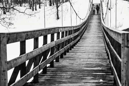 in the black-and-white photo are represented two teenagers walk together next to an old pedestrian suspended wooden bridge and light snow falls