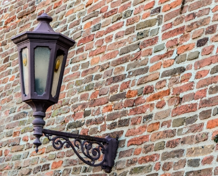 Old street lamp on brick wall