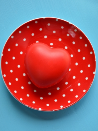 Heart on red plate of polka dots on blue background photo