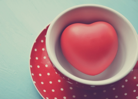 Red polka dot cup of coffee with heart inside vintage photo