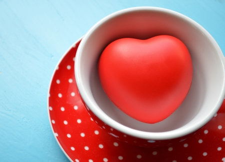 Red polka dot cup of coffee with heart inside  photo