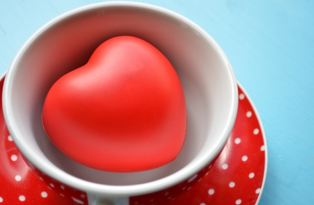 Red polka dot cup of coffee with heart  photo